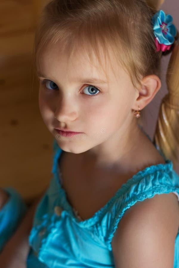 Portret van een mooi zoet meisje in een blauwe kleding met blauwe ogen royalty-vrije stock afbeeldingen