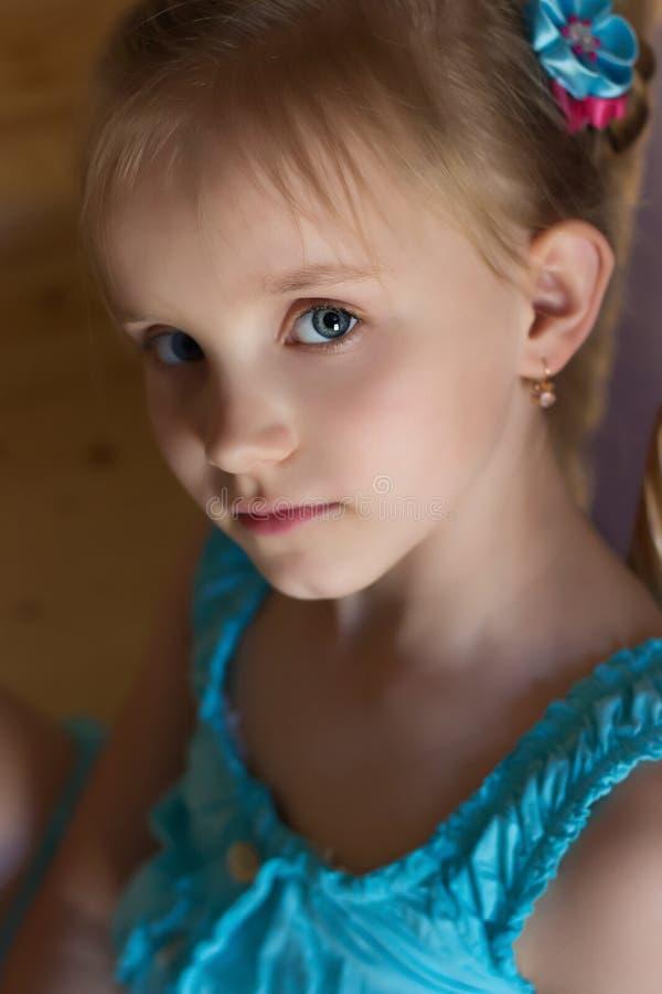 Portret van een mooi zoet meisje in een blauwe kleding met blauwe ogen royalty-vrije stock foto