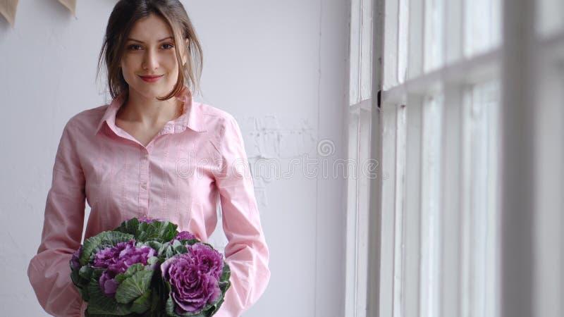 Portret van een mooie bloemist met een violet boeket van ongebruikelijke bloemen - brassica kijk in de camera stock afbeeldingen