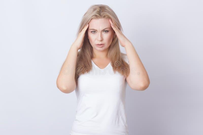 Portret van een mooie blondevrouw met lang haar die hoofdpijn hebben stock foto's