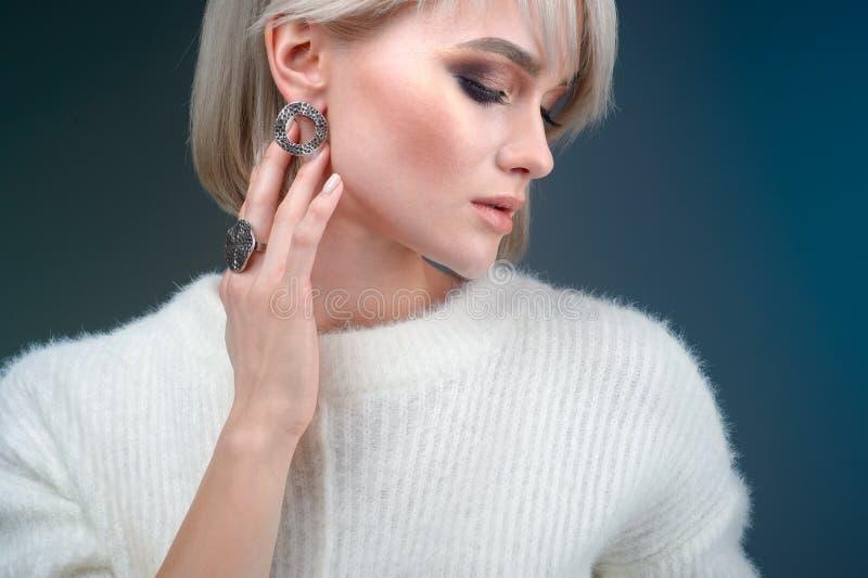 Portret van een mooie blondevrouw met een mooie ring en oorringen die in de studio op een blauwe achtergrond stellen stock afbeelding