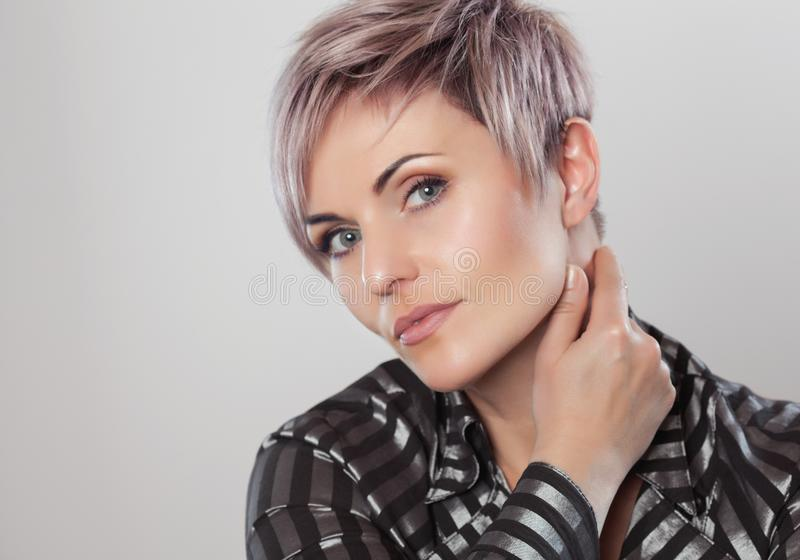 Portret van een mooie blondevrouw met mooie samenstelling en kort kapsel na het verven van haar stock foto's
