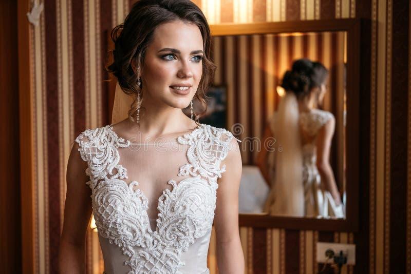 Portret van een mooie bruid in een huwelijkskleding die zich in een ruimte dichtbij een spiegel bevinden royalty-vrije stock afbeelding