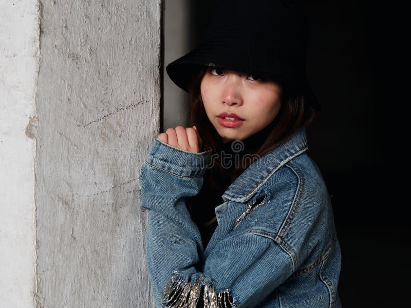 Portret van een mooie Chinese vrouw die in jeans en zwarte hoed recht camera, leuk meisje met glanzende ogen bekijken stock fotografie