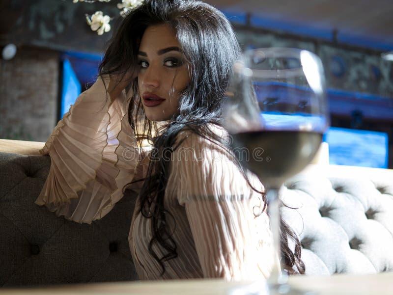 Portret van een mooie donkerbruine meisjeszitting bij de lijst met een glas rode wijn stock afbeeldingen