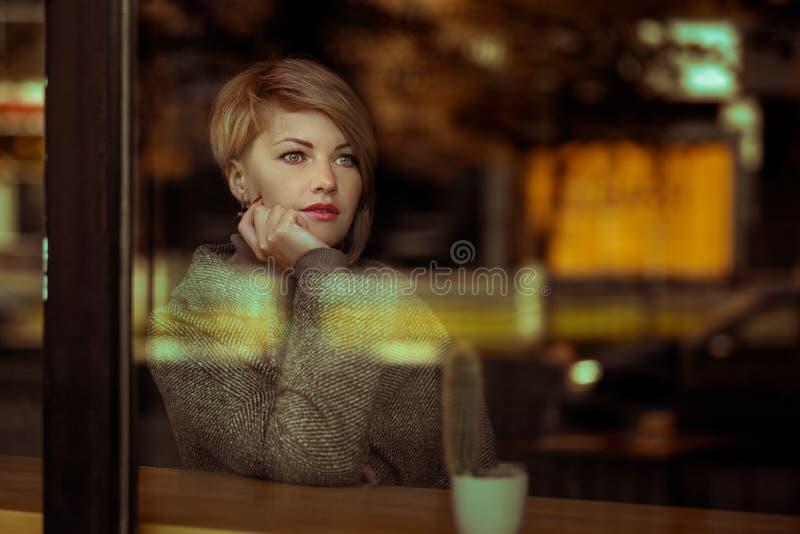 Portret van een mooie elegante vrouw door het glas royalty-vrije stock foto