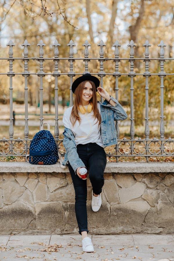 Portret van een mooie glimlachende hipster studente met bruin haar die een hoed, een rugzak en gele hoofdtelefoons binnen dragen royalty-vrije stock fotografie