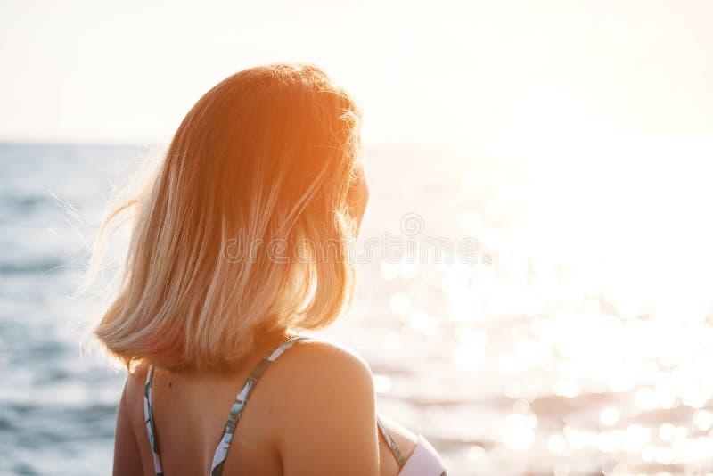 Portret van een mooie glimlachende jonge vrouw in bikini op het strand Het vrouwelijke model stellen in zwempak op overzeese kust royalty-vrije stock foto