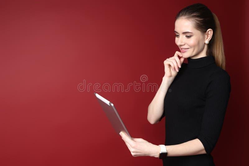 Portret van een mooie glimlachende Kaukasische vrouw die aan tablet op een rode achtergrond werken stock afbeelding