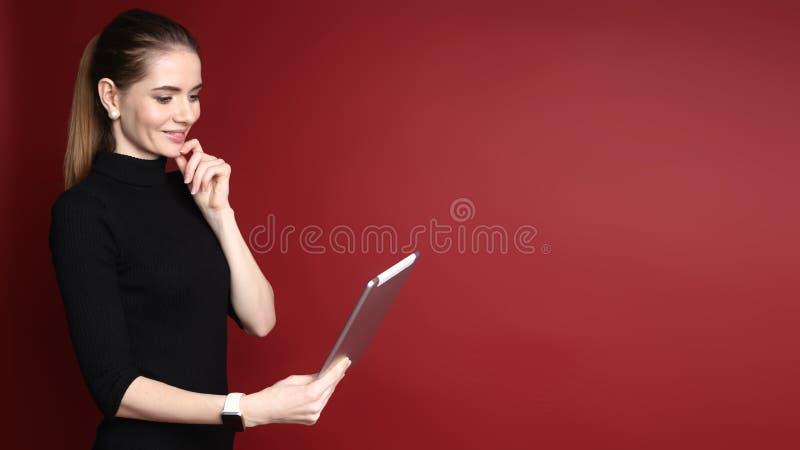 Portret van een mooie glimlachende Kaukasische vrouw die aan tablet werken die op een rode achtergrond wordt ge?soleerd stock afbeeldingen