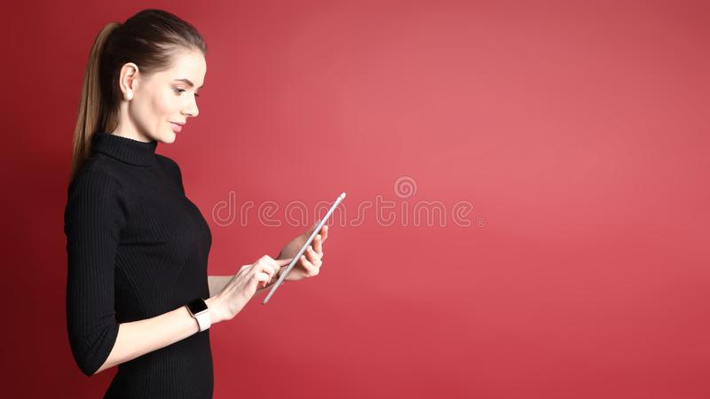 Portret van een mooie glimlachende Kaukasische vrouw die aan tablet werken die op een rode achtergrond wordt ge?soleerd royalty-vrije stock afbeeldingen