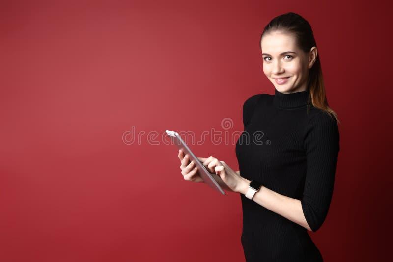 Portret van een mooie glimlachende Kaukasische vrouw in een zwarte kleding die een tablet op een rode achtergrond gebruiken royalty-vrije stock fotografie