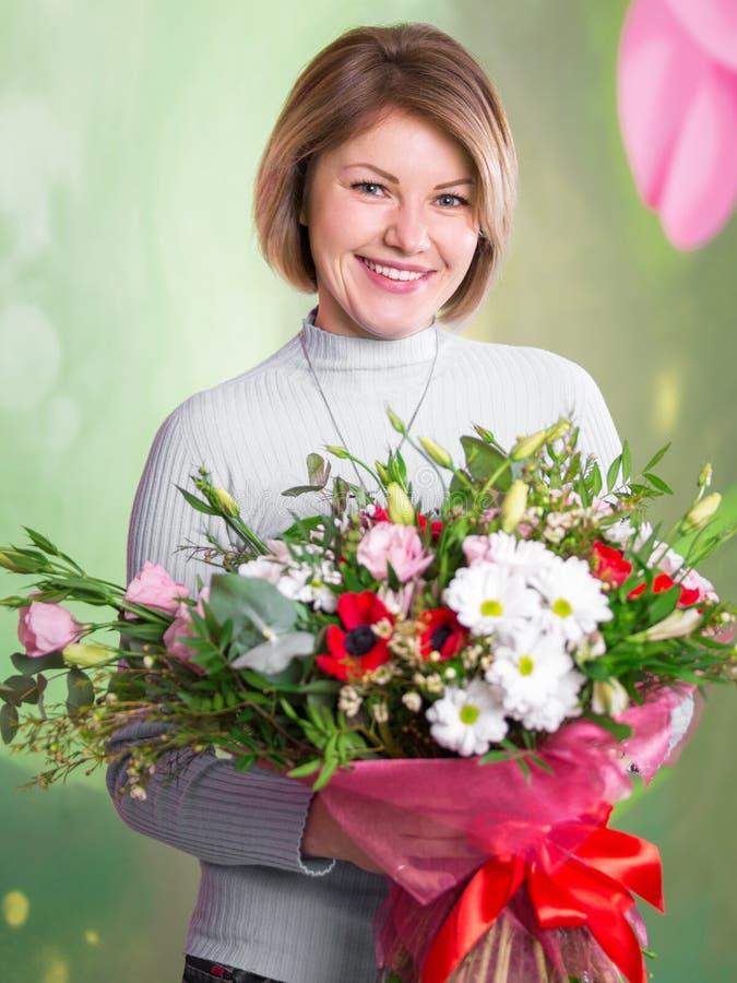 Portret van een mooie glimlachende vrouw met een groot boeket van bloemen royalty-vrije stock fotografie