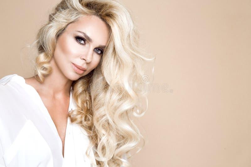 Portret van een mooie, glimlachende vrouw met lang blondehaar en witte tanden royalty-vrije stock foto