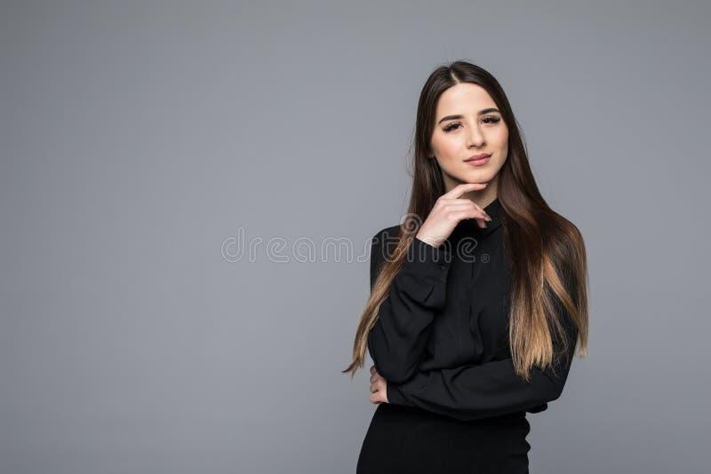 Portret van een mooie jonge bedrijfsvrouw tegen grijze achtergrond royalty-vrije stock afbeelding
