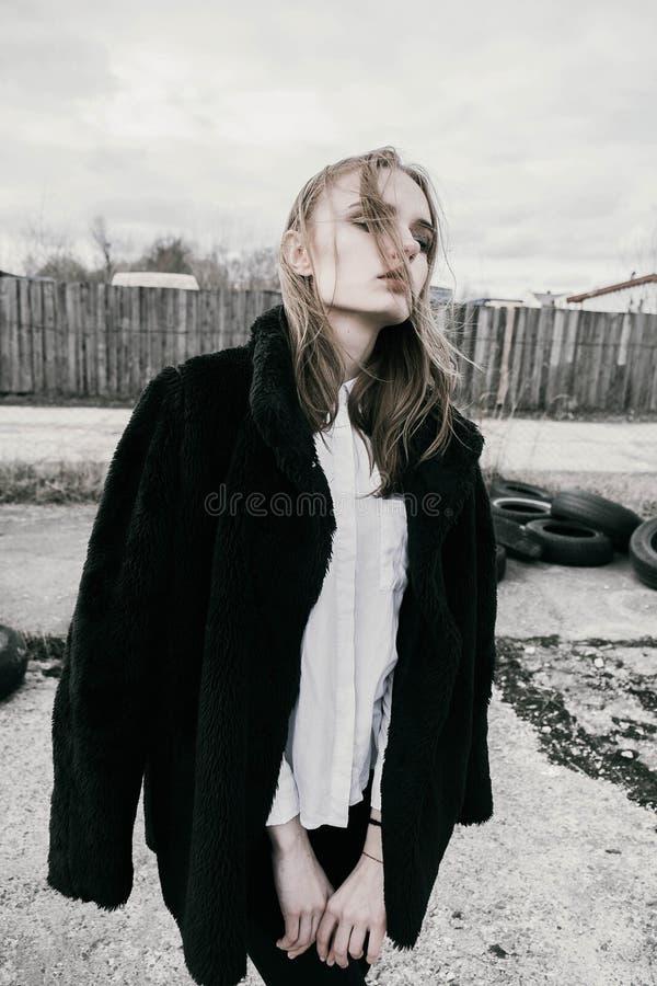 Portret van een mooie jonge bewolkt blondevrouw in een zwart jasje op de straat, stock afbeeldingen