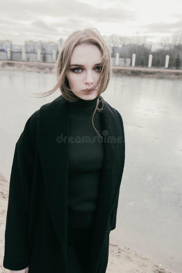 Portret van een mooie jonge bewolkt blondevrouw in een zwart jasje op de straat, stock foto