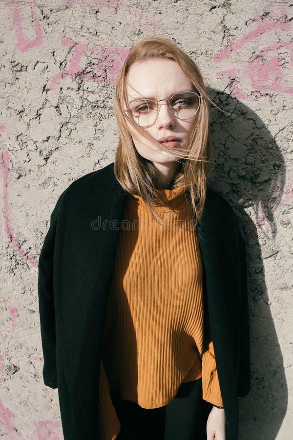 Portret van een mooie jonge blonde vrouw met glazen in de straat royalty-vrije stock foto's