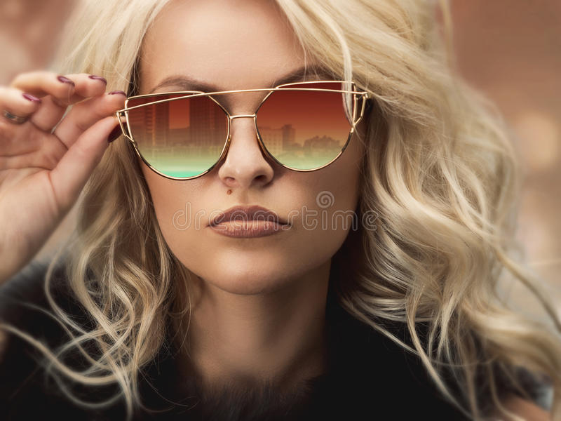 Portret van een mooie jonge blonde vrouw in zonnebril stock afbeeldingen