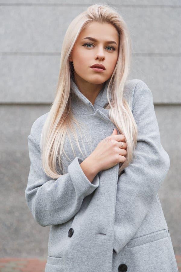 Portret van een mooie jonge blondhairvrouw in grijze laag De straatmanier ziet eruit royalty-vrije stock afbeeldingen