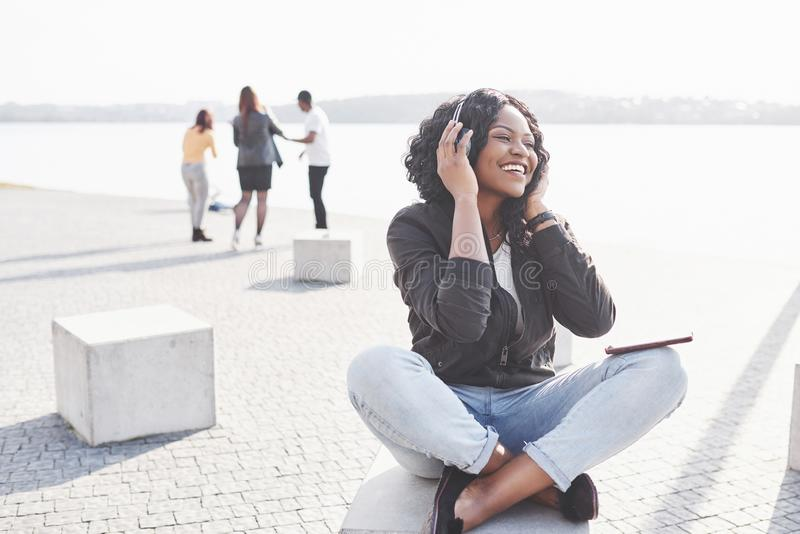 Portret van een mooie jonge vrij Afrikaanse Amerikaanse meisjeszitting op het strand of het meer en het luisteren aan muziek in h stock afbeeldingen