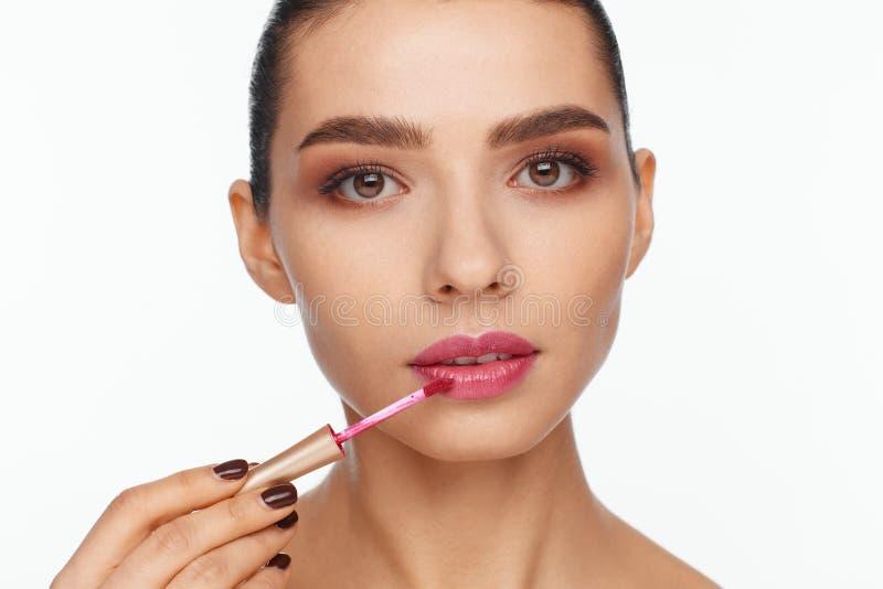 Portret van een mooie jonge vrouw die lippenstift op haar lippen zetten royalty-vrije stock afbeelding