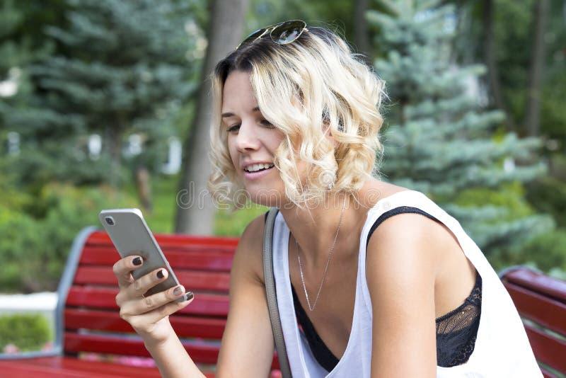 Portret van een mooie jonge vrouw die mobiele telefoon met behulp van stock foto's