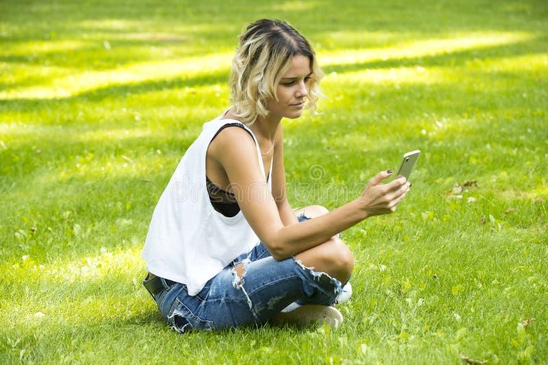 Portret van een mooie jonge vrouw die mobiele telefoon met behulp van royalty-vrije stock afbeelding