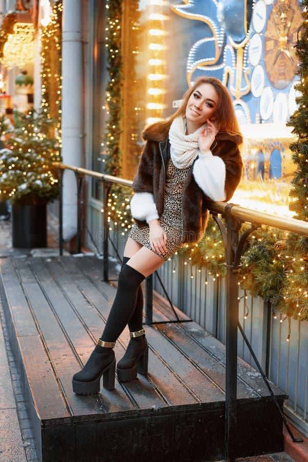 Portret van een mooie jonge vrouw die op de straat dichtbij het elegant verfraaide Kerstmisvenster, feestelijke stemming stelt royalty-vrije stock foto