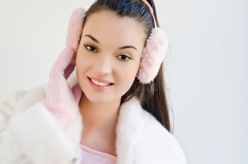 Portret van een mooie jonge vrouw die roze oormoffen en handschoenen dragen royalty-vrije stock foto's