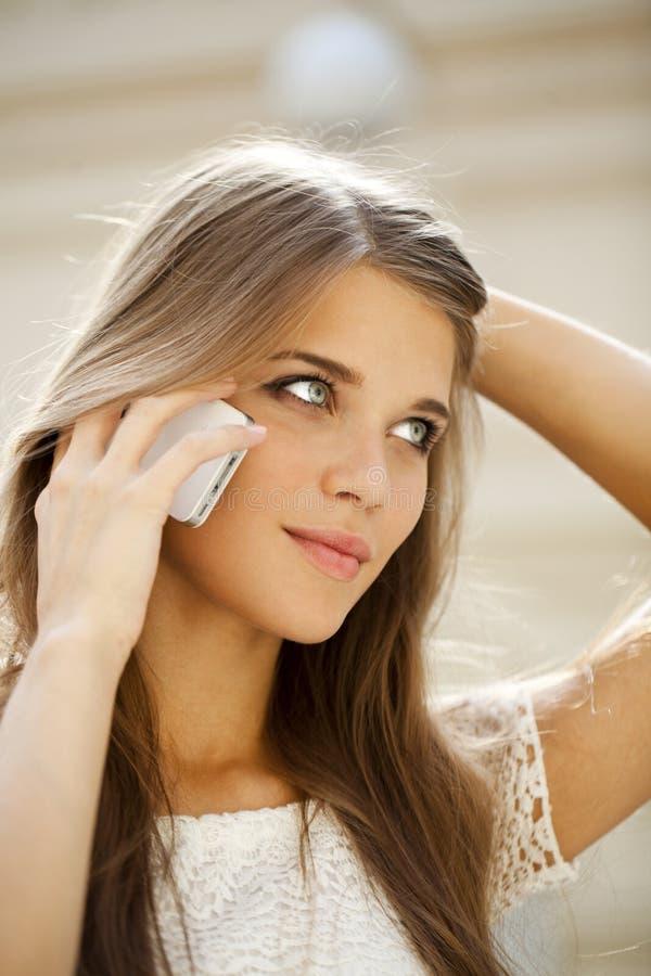 Portret van een mooie jonge vrouw die telefonisch roepen royalty-vrije stock afbeeldingen