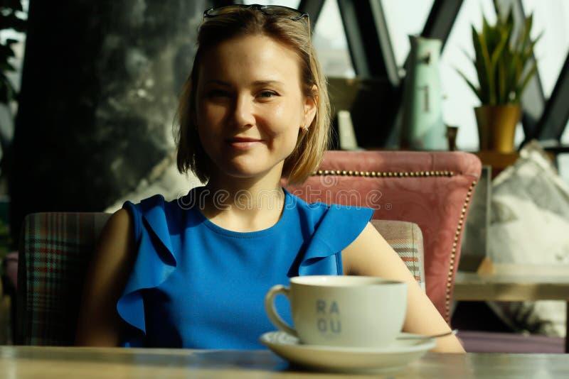 Portret van een mooie jonge vrouw met een kop van koffie in een restaurant Bedrijfs lunch royalty-vrije stock fotografie
