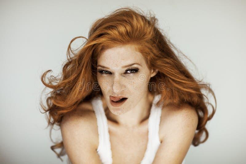 Portret van een mooie jonge vrouw met lange rode krullende haar en sproeten royalty-vrije stock afbeeldingen