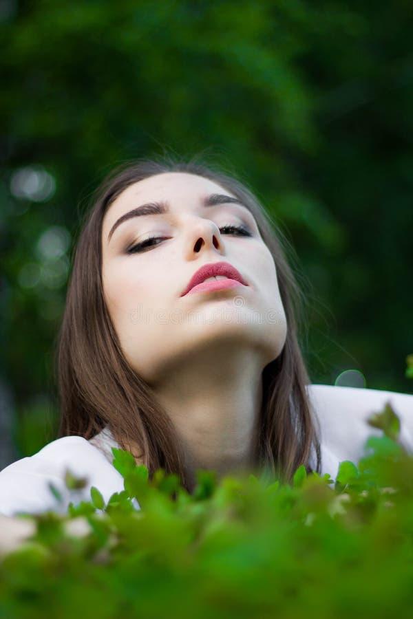 Portret van een mooie jonge vrouw op een achtergrond van groene bladeren, de zomer in openlucht Natuurlijk mooie vrouw die terwij stock foto's