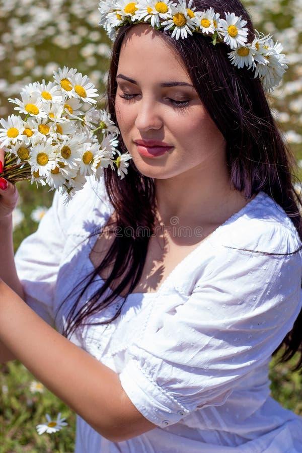 Portret van een mooie jonge vrouw op kamillegebied Gelukkig meisje dat madeliefjes verzamelt Een meisje dat op een gebied van kam royalty-vrije stock afbeeldingen