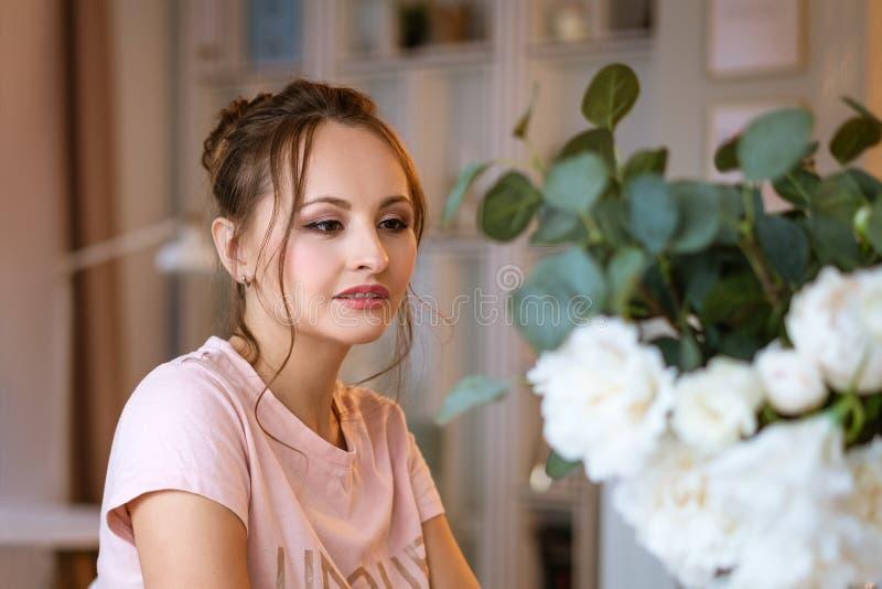 Portret van een mooie jonge vrouw thuis, een bloesem royalty-vrije stock foto