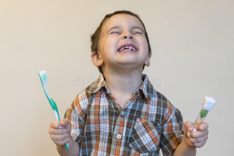 portret van een mooie leuke Kaukasische blonde jongen met een tandenborstel Weinig jongen het borstelen tanden en het glimlachen  stock afbeelding