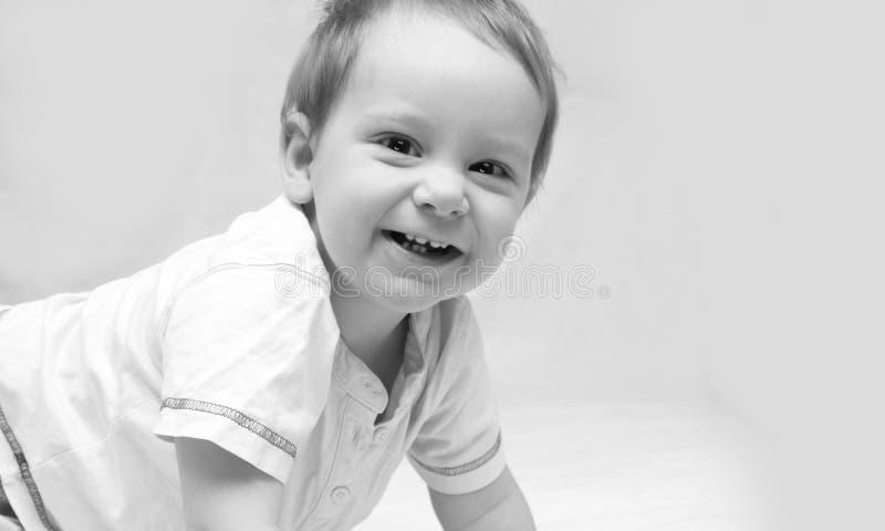 Portret van een mooie 6 maandenbaby die, op witte achtergrond glimlachen stock foto