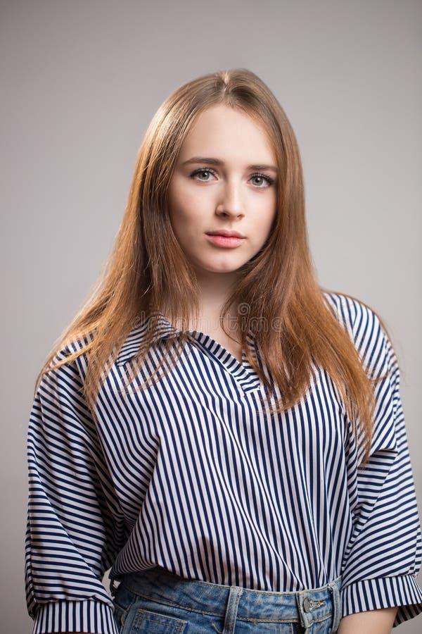 Portret van een mooie roodharigevrouw die een gestreepte blouse dragen en de camera op een grijze achtergrond bekijken Het jonge  royalty-vrije stock foto's