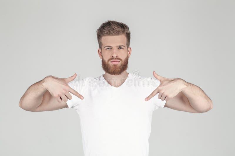 Portret van een mooie sexy hipster gekleed in een witte T-shirt Toont handen op zijn T-shirt plaats voor uw embleem of stock afbeeldingen