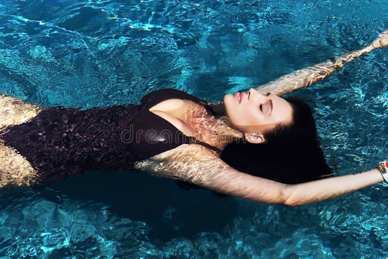 Portret van een mooie sexy vrouw die in de pool zwemmen stock fotografie
