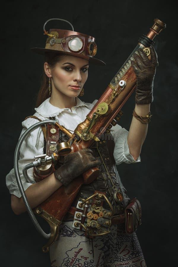 Portret van een mooie steampunkvrouw die een kanon houden stock foto