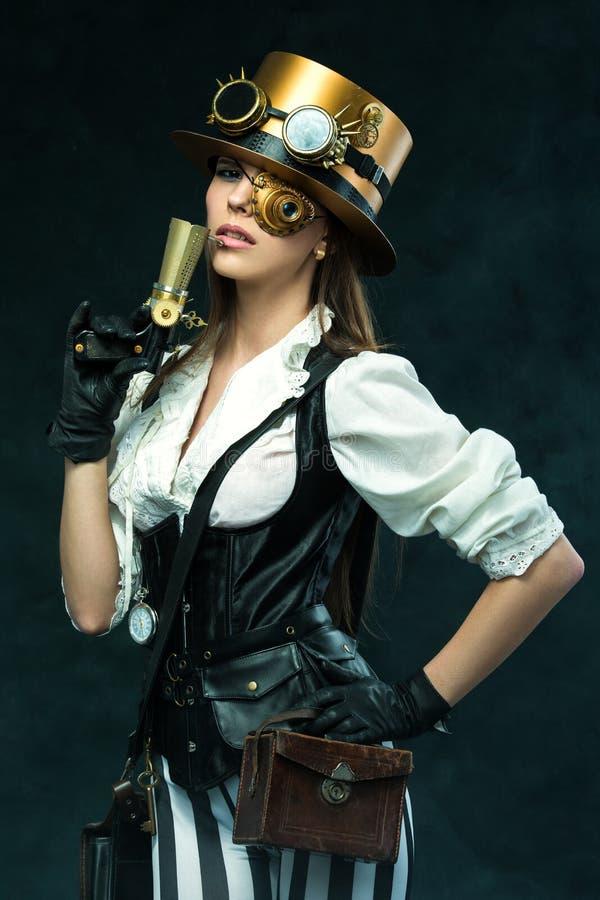 Portret van een mooie steampunkvrouw die een kanon houden stock foto's