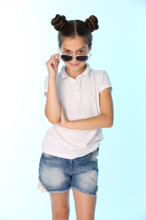 Portret van een mooie tiener 12 jaar oud in een denimborrels met naakte benen, kijkt zij koel stock afbeeldingen