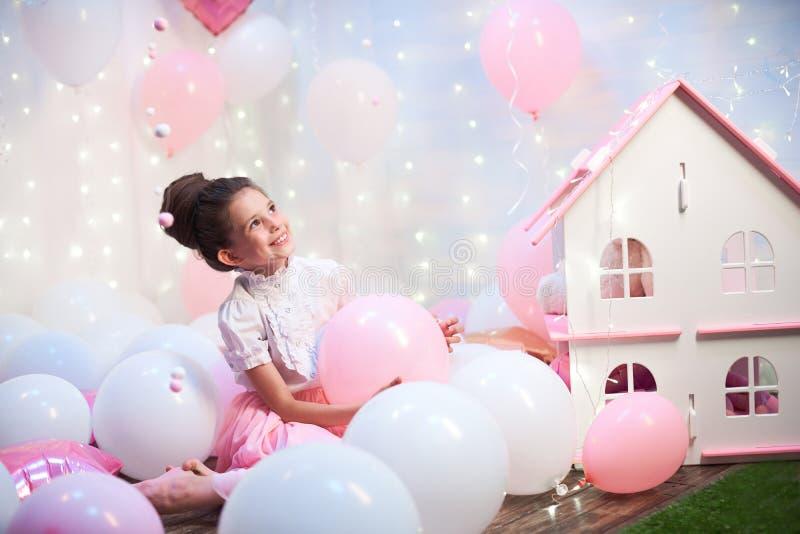 Portret van een mooie tiener in een weelderige roze rok in het landschap van ballons folie en latexballons met helium worden gevu royalty-vrije stock fotografie