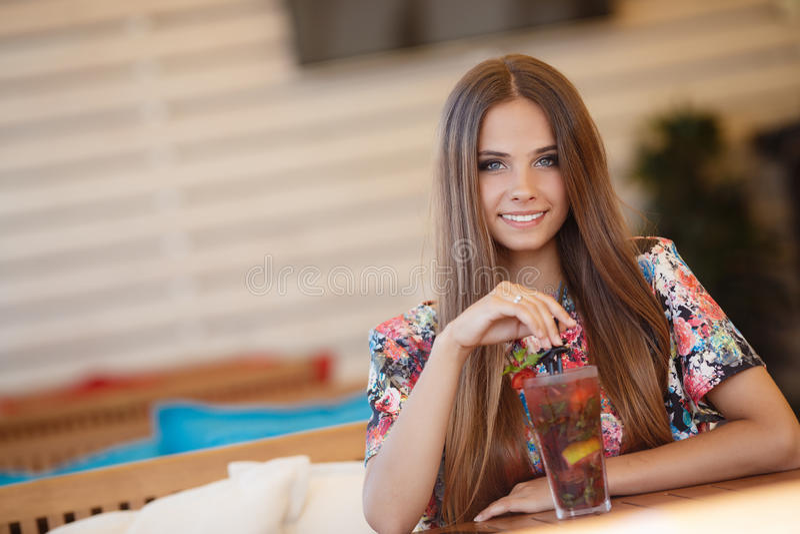 Portret van een mooie vrouw bij een lijst in de zomerkoffie stock foto's