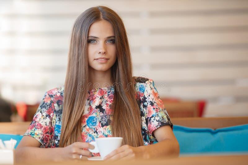 Portret van een mooie vrouw bij een lijst in de zomerkoffie royalty-vrije stock afbeelding