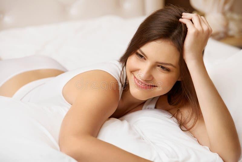 Portret van een mooie vrouw die in bed ontspannen stock foto's