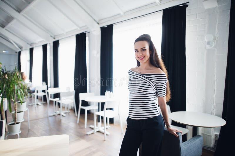 Portret van een mooie vrouw die de camera dichtbij groot venster bekijken Volwassen koffieeigenaar met een het welkom heten gliml royalty-vrije stock afbeelding