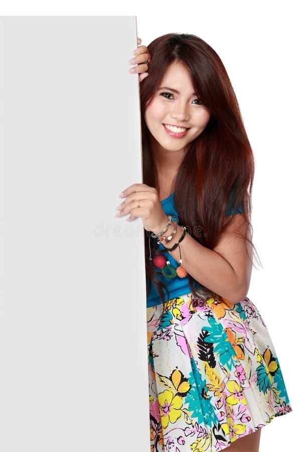 Portret van een mooie vrouw die een leeg aanplakbord houden stock foto